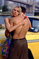 woman holding a rose and a man in New York City by a taxi cab