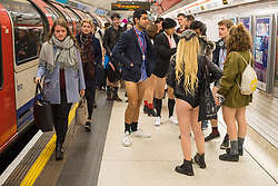 People wait on the platform at Liverpool Street tube station as they take part in No Trousers on the Tube day, in London.