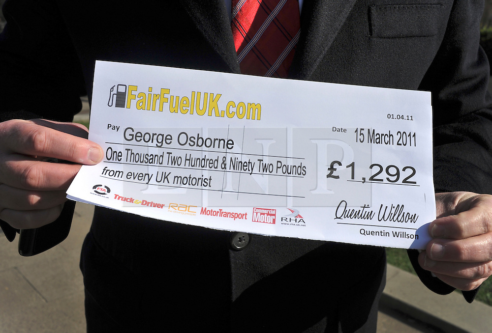 ©London News pictures. 10/03/11.A protester holds up a fair fuel 'cheque' representing the amount of duty an average motorist pays of fuel duty per year. Quentin Willson leads a Fuel Tax protest on College Green outside Parliament, holding a giant cheque to represent the £26 billion Britons pay in fuel duty each year, the campaign was organised by www.fairfueluk.com. Picture Credit should read Stephen Simpson/LNP