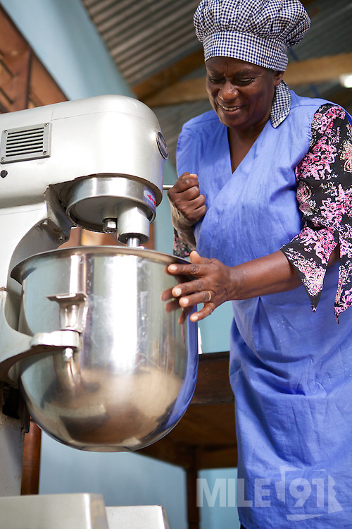 Joyce Marwa using her food mixer. <br /> <br /> Joyce set up and now runs a bakery that bakes bread and cakes. She also processes nutritious flour (a mix of 5 grains)<br /> <br /> She attended MKUBWA enterprise training run by the Tanzania Gatsby Trust in partnership with The Cherie Blair Foundation for Women.