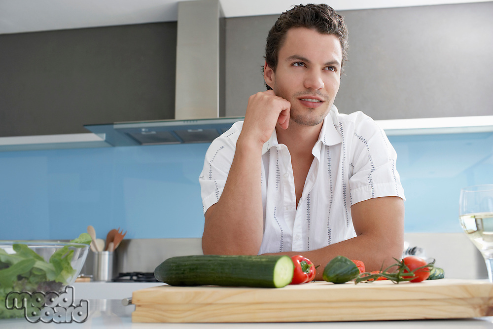 Young man leaning on kitchen counter near cutting board with vegetables hand on chin