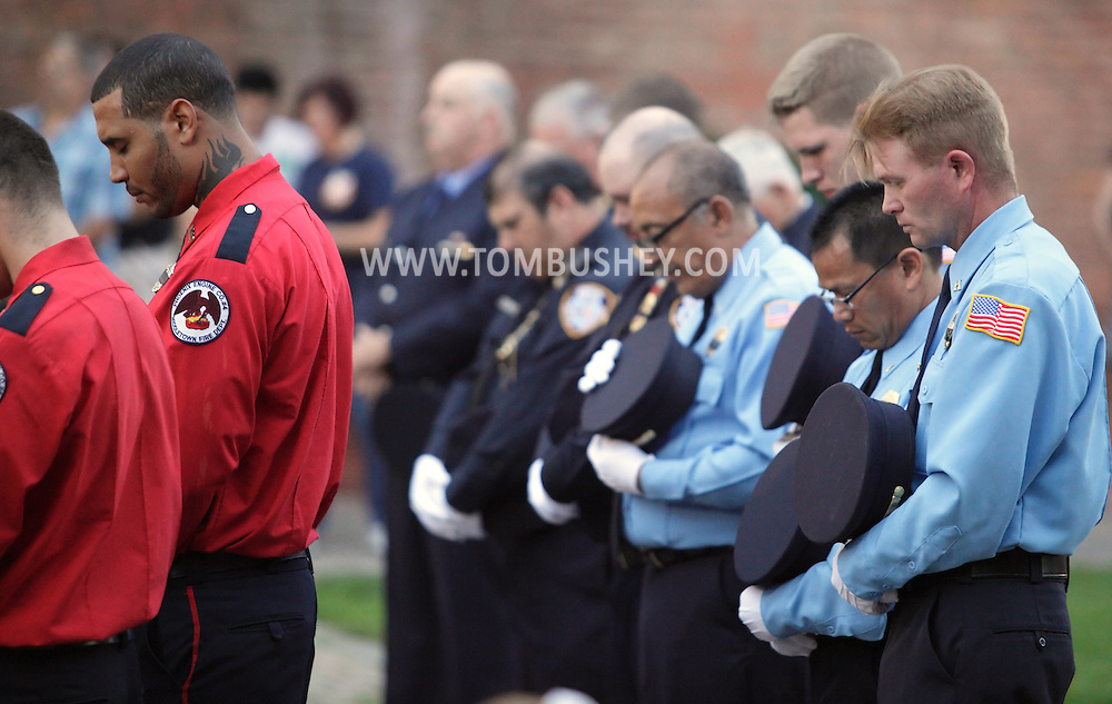 Middletown, New York - Firefighters in dress uniforms bow their heads at the start of the Middletown Fire Department 9/11 Memorial Service at Festival Square on Sept. 11, 2011.