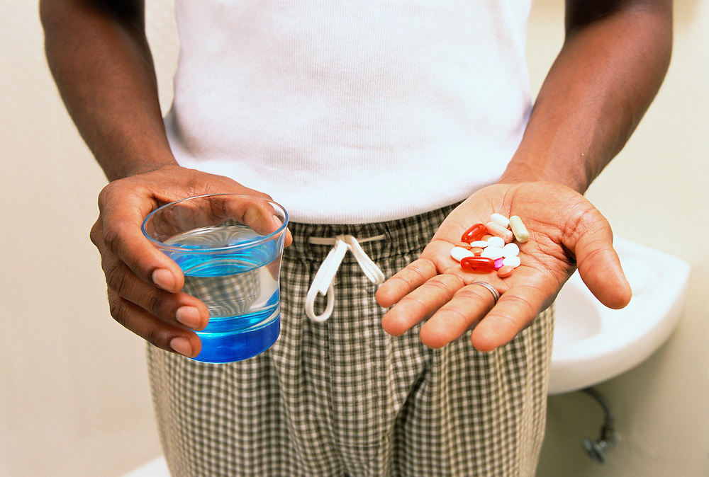 Closeup of a mans hands holding a bunch of pills in one hand and a glass of water in the other.