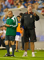 PODGORICA, MONTENEGRO - Wednesday, August 12, 2009: Wales' manager John Toshack MBE clashes with the referee after a horrifically late challenge from Montenegro's Miodrag Dzudovic during an international friendly match at the Gradski Stadion. (Photo by David Rawcliffe/Propaganda)
