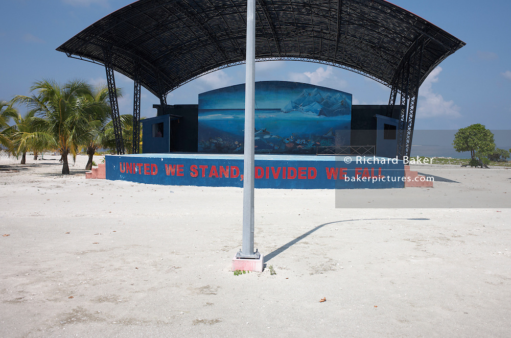 Government slogan urging political unity painted on a communal stage under tropical sun on Meedu Island in Republic of Maldives