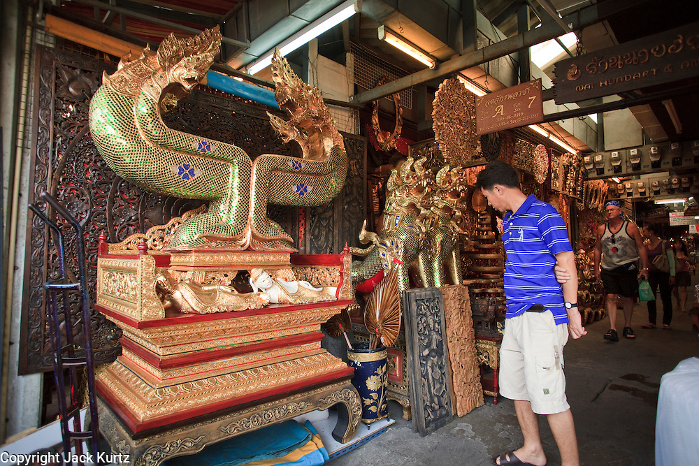 """Mar. 8, 2009 -- BANGKOK, THAILAND: A man looks at """"nagas"""" (serpents in Buddhist mythology) in the Chatuchak Weekend Market. The market covers an area of 35 acres with more than 15,000 shops and stalls. It has over 200,000 visitors each day it's open (Friday - Sunday), and they spend an estimated total of 30 million baht (approx US$750,000). The range of products on sale is extensive, and includes household accessories, handicrafts, religious artifacts, art, antiques, live animals (which unfortunately are frequently caged in cruel conditions), books, music, clothes, food, plants and flowers. Photo by Jack Kurtz / ZUMA Press"""