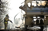 JEROME A. POLLOS/Press..Coeur d'Alene firefighters saturate a smoldering fifth-wheel trailer after the flames were extinguished Thursday morning near 15th Street and Gilbert Avenue. No injuries were reported in the fire that is believed to have started with an electrical problem.