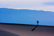 Lone photographer hiking on sand dunes in Death Valley National Park, California