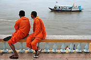 Cambodian Buddhist monks taking in the fresh air along Sisowath Quay in Phnom Penh.  The riverfront road is lined with dozens of restaurants and bars offering curbside seating and a range of hotels and guesthouses, some with riverside views.