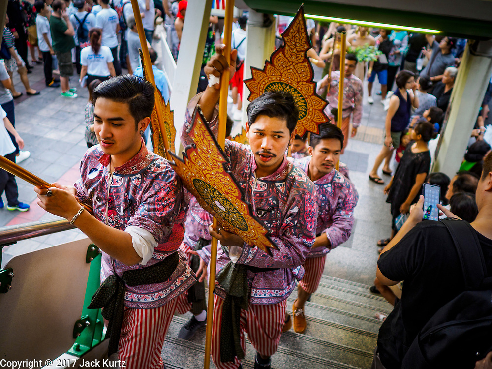 """08 APRIL 2017 - BANGKOK, THAILAND: Entertainers go up the stairs into the Phrom Phong BTS station at the """"Amazing Songkran"""" festival in Benchasiri Park in Bangkok. The festival was sponsored by the Tourism Authority of Thailand to highlight the cultural aspects of Songkran. Songkran is celebrated in Thailand as the traditional New Year's Day from 13 to 16 April. Songkran is in the hottest time of the year in Thailand, at the end of the dry season and provides an excuse for people to cool off in friendly water fights that take place throughout the country. Songkran has been a national holiday since 1940, when Thailand moved the first day of the year to January 1. Songkran 2017 is expected to be more subdued than Songkran usually is because Thais are still mourning the October 2016 death of revered King Bhumibol Adulyadej.       PHOTO BY JACK KURTZ"""