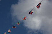 British flags on a string waving in the breeze against sky and cloud