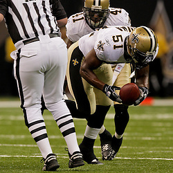 2009 August 14: New Orleans Saints linebacker Jonathan Vilma (51) scoops up a fumble during  the first quarter of a preseason opener between the Cincinnati Bengals and the New Orleans Saints at the Louisiana Superdome in New Orleans, Louisiana.
