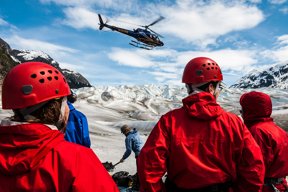 Tourists watch a helicopter depart from the Juneau Icefield, Alaska.