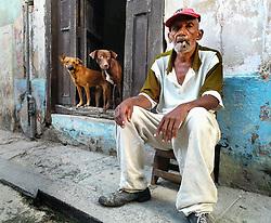 Old man smoking cigar, sitting. Doorway, open door, dogs.