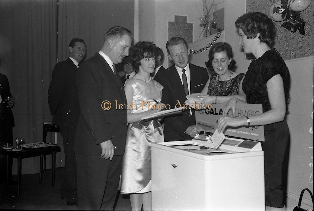 17/12/1962<br /> 12/17/1962<br /> 17 December 1962<br /> A.E.I. Gala reception at Shangri-la Hotel, Dalkey, Dublin, where a Gala Supermatic washing machine was presented to the Variety Club of Ireland for their Easter Draw by Gala. At the function were Des O'Keefe, Chief Barker, Variety Club of Ireland; Patricia Kavanagh, (Gala Demonstrator); Mr. P.N. Walsh, Area Manager for Ireland; Aine Twomey, (Gala Demonstrator) and Annette Vahey, (Gala Demonstrator) drawing the tickets for the lucky winners in the Gala &quot;Take your chance&quot; promotion for purchasers of Gala products.