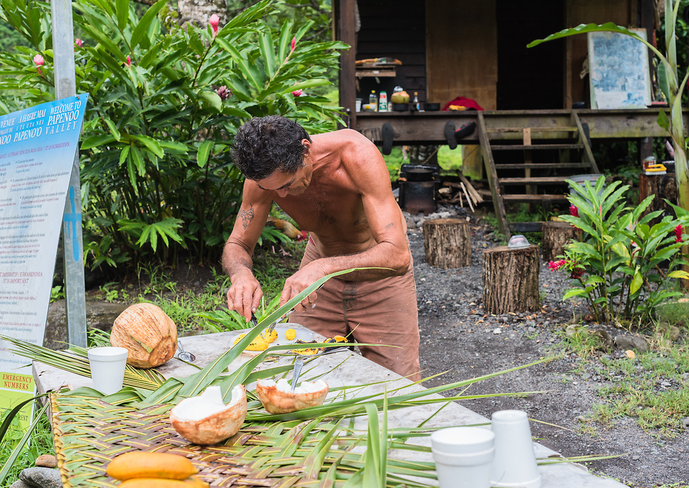 Tahiti, French Polynesia--March 18, 2018. A Tahitian man prepares produce at his food stand. Editorial Use Only.