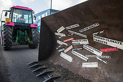 London, UK. 8 December, 2019. Climate activists from Extinction Rebellion use a full-scale mock-up of a bulldozer outside Heathrow airport for a Bikes Against Bulldozers protest against Heathrow expansion and the greenwashing of climate commitments by political parties. The protest took the form of a Critical Mass bicycle ride from Hyde Park followed by a lie-in in front of the bulldozer to which Boris Johnson and John McDonnell were invited in order to fulfil their pledge of lying down in front of bulldozers to be used for Heathrow expansion.