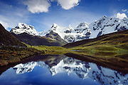 The peaks of Carnicero (right, 19,550 feet / 5960 meters) and Trapecio (left, 18,550 feet / 5653 meters) reflect in a lake at 15,000 feet elevation, in the Cordillera Huayhuash, Andes Mountains, Peru, South America. Published in Wilderness Travel 2011 Catalog of Adventures.
