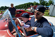 Old Westbury, New York, United States. 7th June 2015. JACKSON STERN, five-months-old, holds the steering wheel of a red 1954 Chevrolet Corvette convertible as he sits in the lap of his father JOSHUA STERN, at the 50th Annual Spring Meet Car Show sponsored by Greater New York Region Antique Automobile Club of America. The Corvette, which was parked, is owned by Adam Heller of NYC. Over 1,000 antique, classic, and custom cars participated at the popular Long Island vintage car show held at historic Old Westbury Gardens.