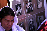 SPECIAL OLYMPICS AFGHANISTAN..KABUL 24 August 2005..Bagh-e-Zanana, female games...Youn Afghan woman, wearing a white veil, sits next to a photo exibition installation at the Women Affairs Department...On 23-25 August 2005, Special Olympics Afghanistan held its first national Games at Olympic Stadium in Kabul. More than 300 athletes, including 80 female athletes, experienced a taste of happiness and achievement for the first time in their lives. They competed in athletics, bocce and football (soccer). Because of cultural restrictions, males and females competed at separate venues.