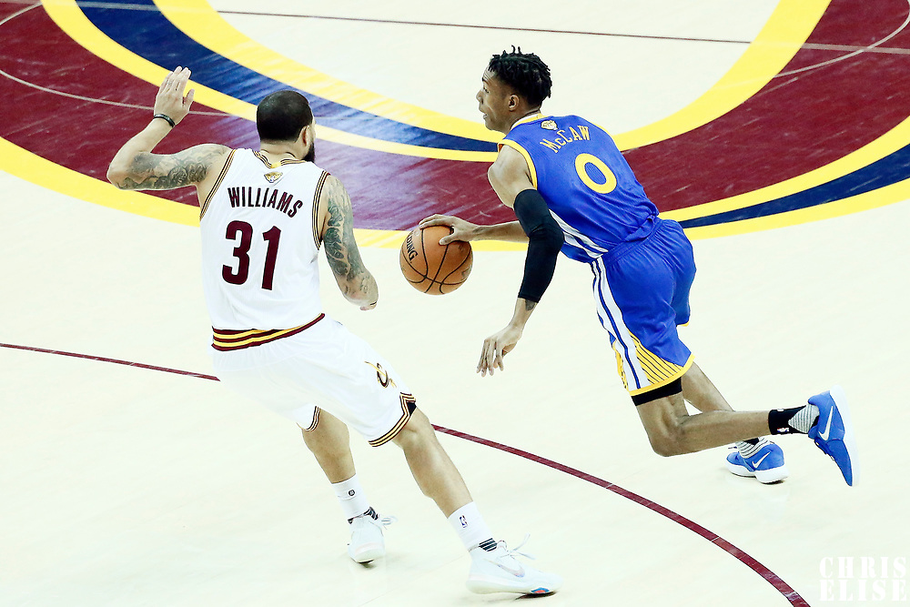 09 June 2017: Golden State Warriors guard Patrick McCaw (0) drives past Cleveland Cavaliers guard Deron Williams (31) during the Cleveland Cavaliers 137-11 victory over the Golden State Warriors, in game 4 of the 2017 NBA Finals, at  the Quicken Loans Arena, Cleveland, Ohio, USA.