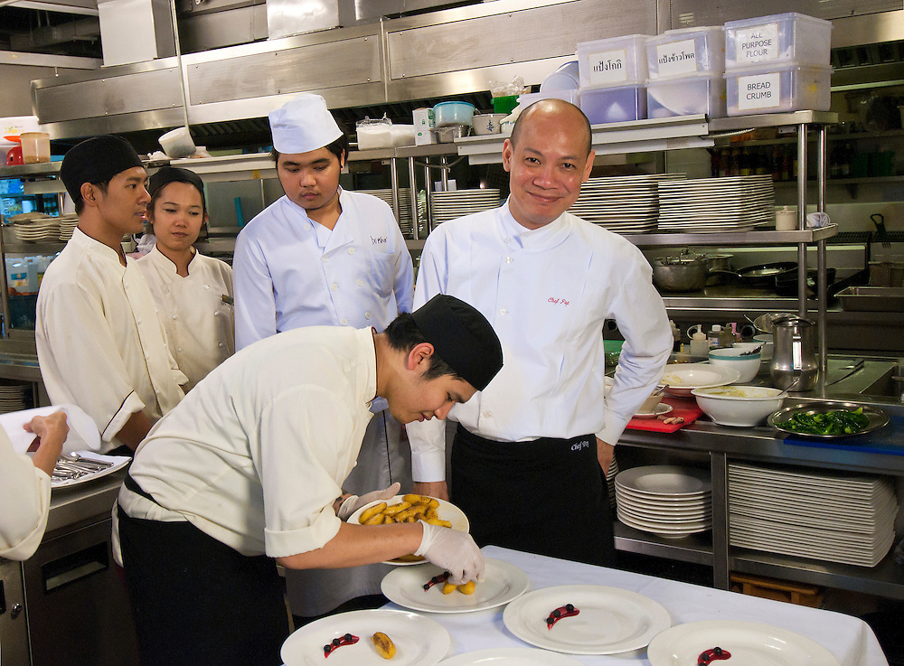 Chef Pop (center) in the kitchen at Maison Chin restaurant in Bangkok founded by Celebrity Chef Ken Hom and Chef Pop, Bangkok, Thailand.  Desert being prepared:  Warm banana compote in plum wine with candied ginger served with vanilla bean pod ice cream.  The dish includes strawberry cheesecake, cr?me brulee on a chocolate biscuit puff pastry, with chocolate, mint, and assorted fresh fruits.
