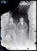 eroding glass plate photo with two men father and son in front of a door opening