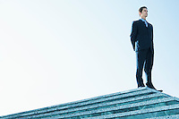 Businessman Standing on marble platform low angle view.