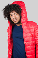 Portrait of young man wearing red jacket with hood over colored background