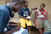Satta Fahnbulleh, 17, interviews a woman while Karn B. Sherman, 17, takes notes as they work on producing a UNICEF-sponsored youth radio program that will air on a local radio station in the town of Sinje, Grand Cape Mount county, Liberia on Friday April 6, 2012. The program is entirely run by teenagers, and discusses various issues related to children's rights, health, education, etc.
