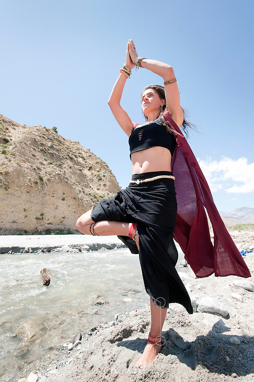 Woman in the yoga pose tree by a flowing river.