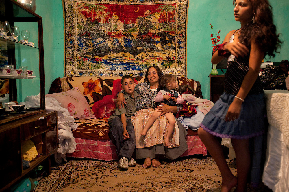 Petrace Marieana sits with her grandkids, Bobi and Miralela, while their neighbor, Florina , arranges her hair in Buzescu, a small town in Romania.