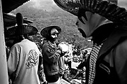 """Oaxaca: Huautla de Jimenez. Day of the Dead: the """"Huehuentones"""", performing the souls coming back, dance and plays in the streets and inside the cemetery. The Dia de Muertos (Day of the Dead), recently declared by UNESCO as an """"oral and intangible cultural heritage of humanity,"""" is one of Mexico's most cherished traditions, celebrated in cities and villages countrywide. Far away from more well-traveled tourist routes, in a Sierrra Madre mountain village near Oaxaca, women speak quietly with beloved departed souls at graves adorned with offerings of food, candies, liquor, cigarettes, evertything their dead  enjoyed while alive. In Huautla de Jimenez local Mazatec Indians still meet their long-gone friends and family in the graveyard, celebrating along with Huehuetones, mysterious masked figures representing the visiting souls from the Underworld."""