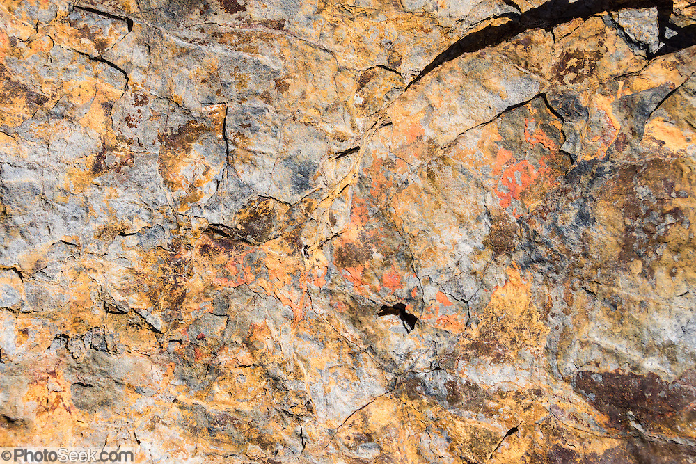 Orange, yellow, and white rock pattern, in Rio Achin Valley. Geology: Cordillera Huayhuash is comprised of uplifted sedimentary sea floor rocks (quartzite, limestone, slate) with a base of granodiorite. Day 9 of 9 days trekking around the Cordillera Huayhuash in the Andes Mountains, near LLamac, Peru, South America.