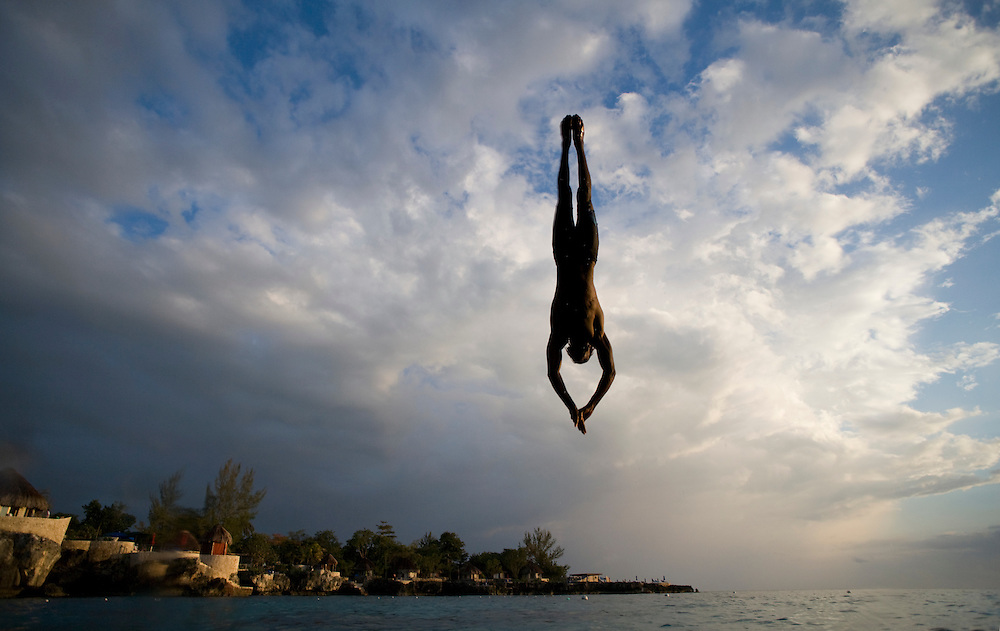 Jamaica, Negril, Silhouette of young man leaping from from cliff above Pirates Cave