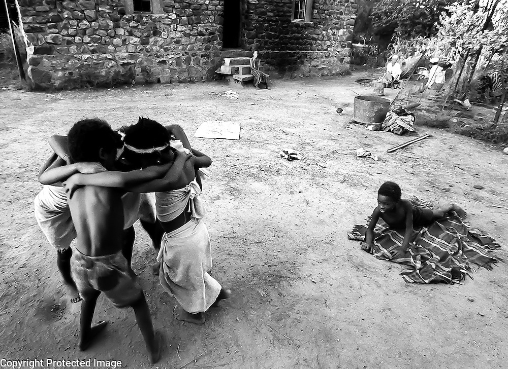 Brenda, her siblings and cousins dance outside their home in a rural area outside of Johannesburg, South Afrca. The children made matching outfits out of some material they found in the trash and decided a performance should follow. With no television and few toys, the Mashila children frequently make up games to entertain themselves using whatever props they find. Despite the fact that apartheid ended 7 years ago, the Mashila family lives much as they would have under the apartheid system.
