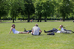 © Licensed to London News Pictures. 18/05/2020. London, UK. Members of the public relax in Finsbury Park, north London as the government relaxes the rules on the COVID-19 lockdown, allowing people to spend more time outdoors whilst following social distancing guidelines. According to the Met Office, warmer weather is forecast this week. Photo credit: Dinendra Haria/LNP