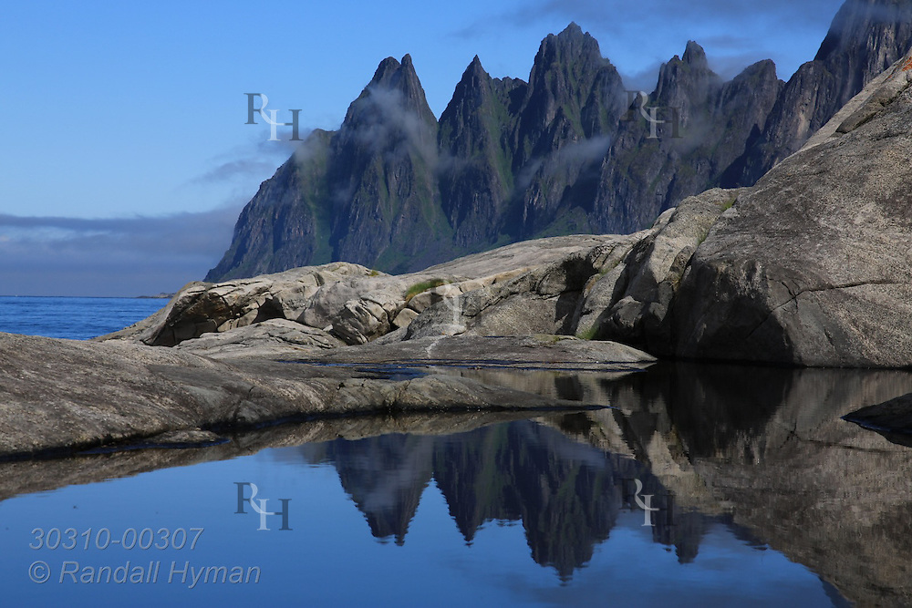 Rocky crags of Devil's Teeth reflect in tidal pool at Tungeneset along National Tourist Route on Senja Island, Norway.