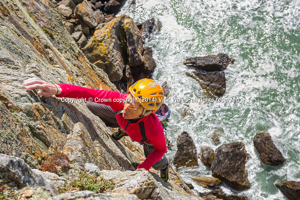 View down from top of cliff to  female climber ascending<br /> Rock Climbing<br /> Rhoscolyn<br /> Holy Island<br /> Anglesey<br /> North<br /> Adventure<br /> Activities and Sports