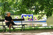 Elderly lady in black resting on a bench on a Sunday afternoon in Lazienki Park, Warsaw, Poland.