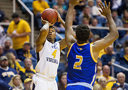 Dec 17, 2016; Morgantown, WV, USA; West Virginia Mountaineers guard Daxter Miles Jr. (4) shoots a three pointer over UMKC Kangaroos guard Isaiah Ross (2) during the second half at WVU Coliseum. Mandatory Credit: Ben Queen-USA TODAY Sports