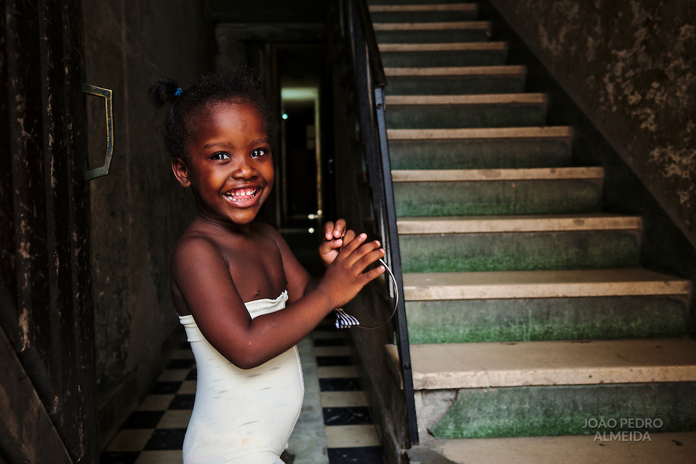 Little girl playing at the entrance of the building of her house at Centro Habana.