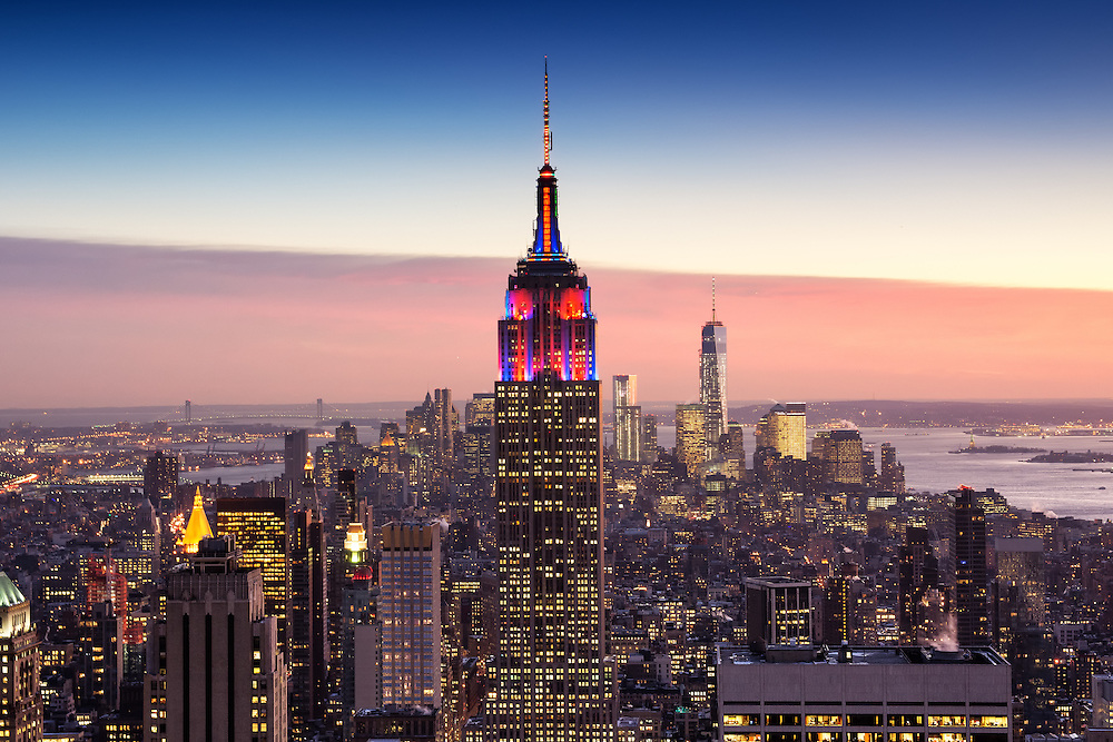 The Empire State Building with a red, white and blue sky