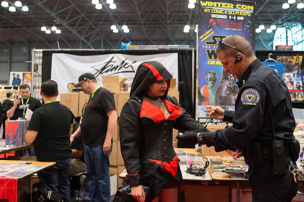 Adaina Velez, left, gets help with her costume from her boyfriend / handler Frank Alvesio, at Comic Con at the Javits Center in New York, NY, on Friday, Oct. 9, 2015. <br /> <br /> Photograph by Andrew Hinderaker