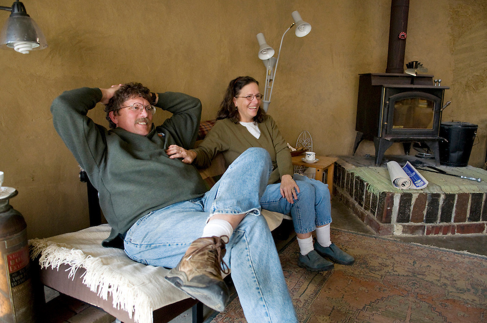 "Jay and Annie Warmke share a laugh in the living room of the ""Earthship."""