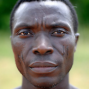 Benin, Tory April 17, 2005 - Man with tribal scarification on his face. It's the 2X5, It's the voodo Python. Scarification is used as a form of initiation into adulthood, beauty and a sign of a village, tribe, and clan.