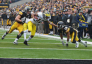 November 05, 2011: Michigan Wolverines wide receiver Roy Roundtree (12) is hit by Iowa Hawkeyes linebacker James Morris (44) and Iowa Hawkeyes cornerback Micah Hyde (18) during the second half of the NCAA football game between the Michigan Wolverines and the Iowa Hawkeyes at Kinnick Stadium in Iowa City, Iowa on Saturday, November 5, 2011. Iowa defeated Michigan 24-16.
