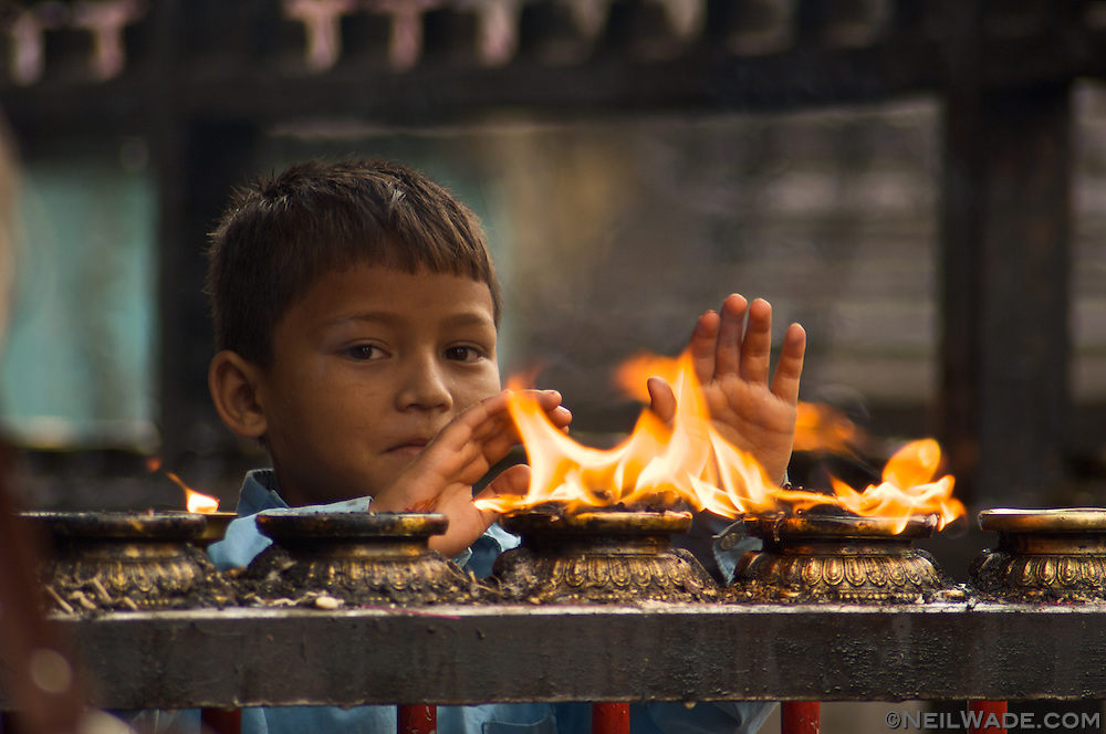 A boy purifies himself with the smoke from holy candles at Swayambunath Stupa in Kathmandu.