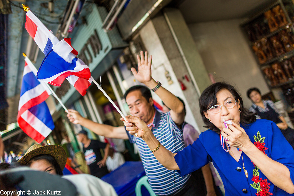 05 JANUARY 2014 - BANGKOK, THAILAND: A woman blows a whistle in support of anti-government protestors passing her in Bangkok. Suthep Thaugsuband, leader of the anti-government protests in Bangkok, led the protestors on a march through the Chinatown district of Bangkok. Tens of thousands of people waving Thai flags and blowing whistles gridlocked what was already one of the most congested parts of the city. The march was intended to be a warm up to their plan by protestors to completely shut down Bangkok starting Jan. 13.     PHOTO BY JACK KURTZ