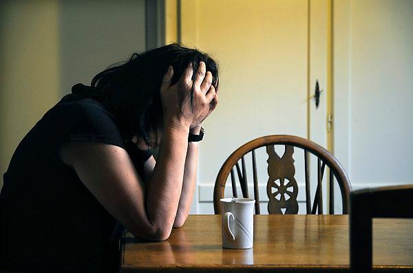 Nederland, Ubbergen, 5-7-2009Foto geensceneerd. Vrouw van middelbare leeftijd zit met de handen in het haar aan de keukentafel.Foto: Flip Franssen